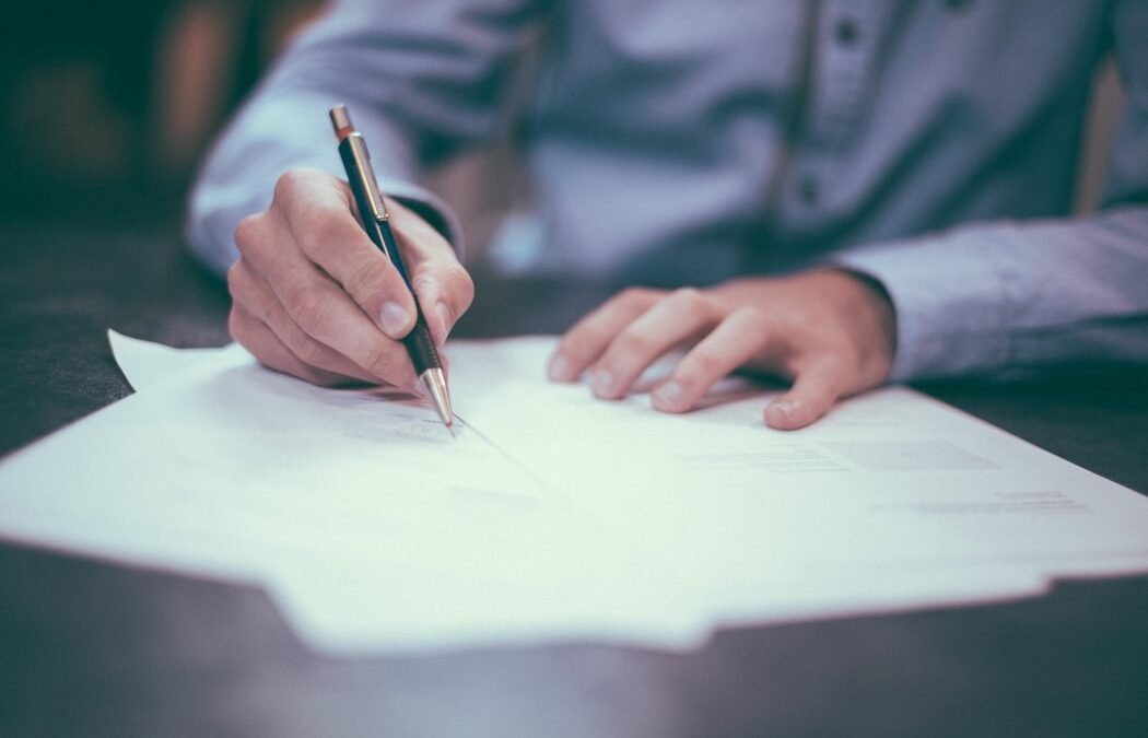 Person writing a contract
